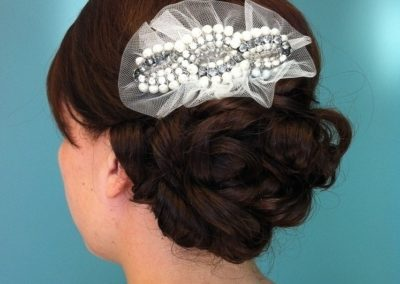 A bride at Details Salon in Mount Joy, PA displays her wedding updo and decorative hair accessory