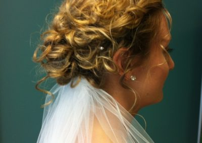 A bride displays her blond curly updo created by Details Salon in Mount Joy, PA