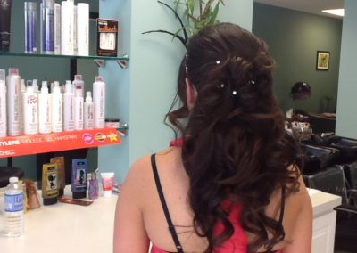 Woman with long brown hair shows off her formal bridal hair style created by Details Salon in Mount Joy, PA