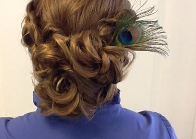 back view of a loosely gathered hair updo compete with a peacock feather created by Details Salon in Mount Joy, PA