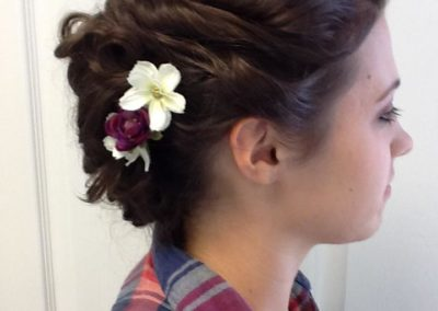 side view of a floral hair piece holding together a bridal up do by Details Salon in Mount Joy, PA