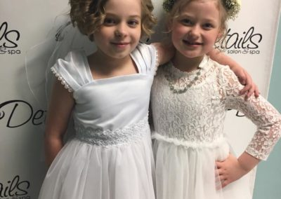 two flower girls pose with bridal up-dos styled by Details Salon