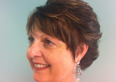 angled view women's haircut and color in Mount Joy, PA - short cropped dark hair with auburn highlights