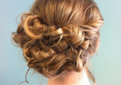 formal updo with loose curls in the middle of her head for a woman at Details Salon