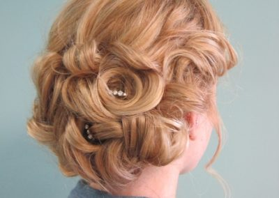 formal updo loosely held with hairpins for a woman with long blonde hair at Details Salon