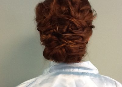 formal updo and beautiful styling for a woman with long dark hair at Details Salon