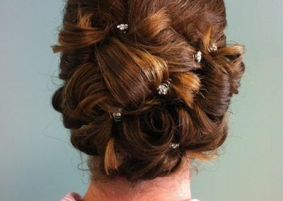 formal updo with decorative hairpins for a woman with long dark hair at Details Salon