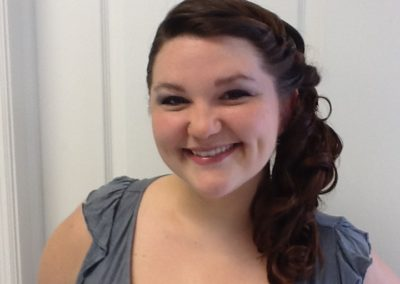 formal updo and makeup for a woman with long dark hair at Details Salon