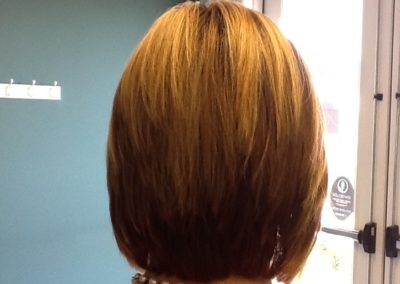back view women's haircut and color in Mount Joy, PA - short red with full highlights