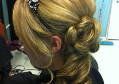 Details Salon customer with long blonde hair shows off her long, styled ponytail done for prom